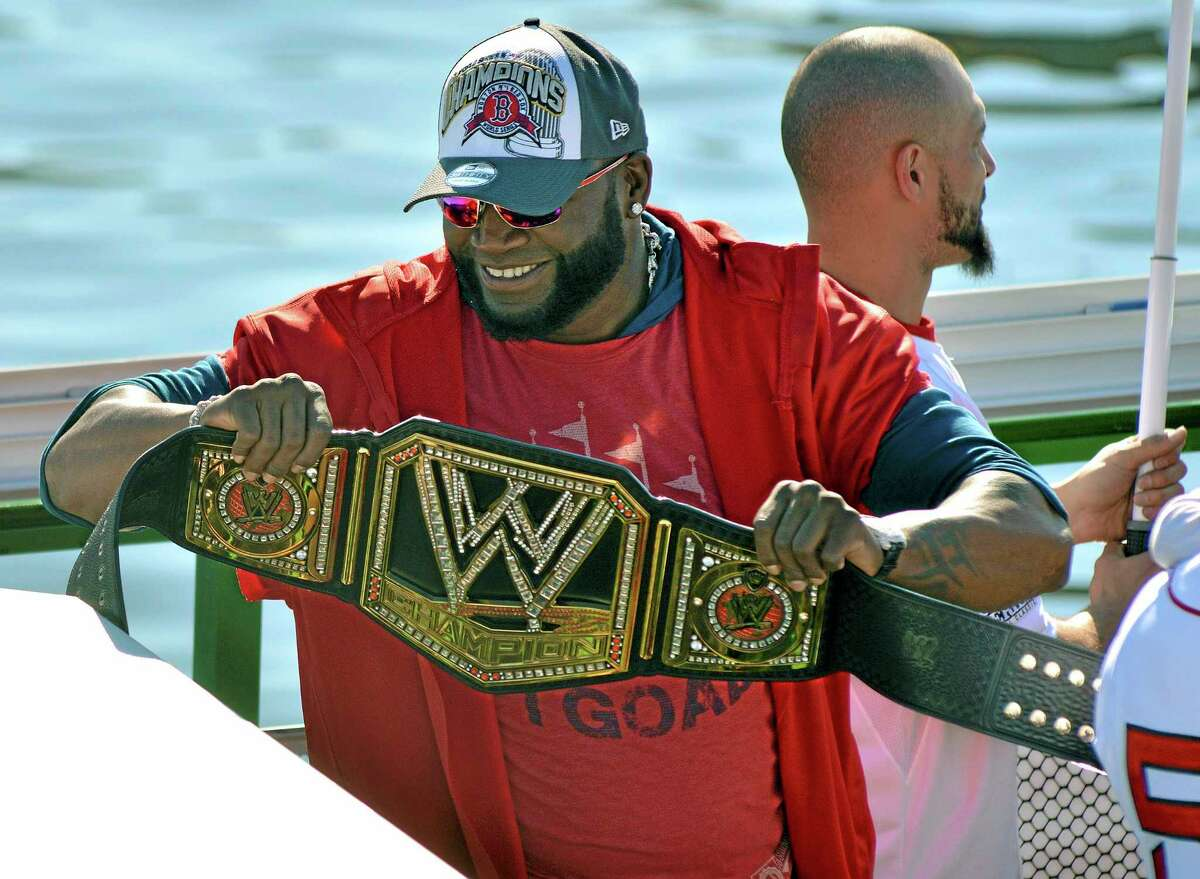 Red Sox designated hitter David Ortiz holds up a championship belt as he and his teammates ride on a duck boat on Saturday on the Charles River in Boston during a rolling parade celebrating the team's World Series title.