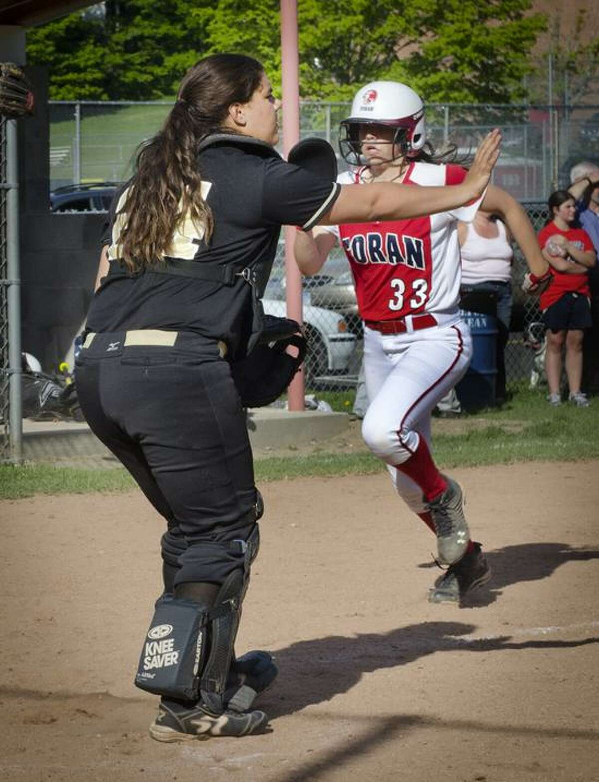 SPORTs-Law Catcher, Amanda Leone, waves off the throw as Foran's Rebekah DeRosa (L) safely crosses the plate Melanie Stengel/Register