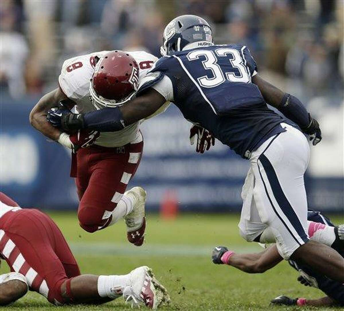 Connecticut linebacker Yawin Smallwood (33) tackles Temple running back Montel Harris (8) in overtime during an NCAA college football game in East Hartford, Conn., Saturday, Oct. 13, 2012. Temple won 17-14. (AP Photo/Michael Dwyer)