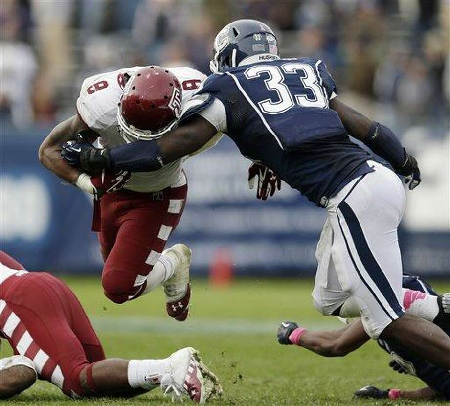 Connecticut linebacker Yawin Smallwood (33) tackles Temple running back Montel Harris (8) in overtime during an NCAA college football game in East Hartford, Conn., Saturday, Oct. 13, 2012. Temple won 17-14. (AP Photo/Michael Dwyer) Photo: ASSOCIATED PRESS / AP2012