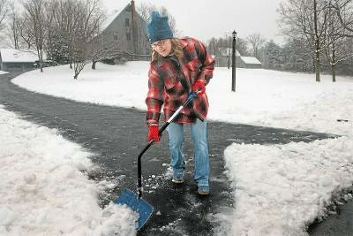 """Catherine Avalone/The Middletown Press Christina Muro reaches the end of shoveling a long driveway at her Durham home Wednesday afternoon. Muro teaches math and social studies to the middle school students at the Watkinson School in Hartford, but school was cancelled today. Referring to the length of the driveway, Muro said, """"Gravity helps."""""""