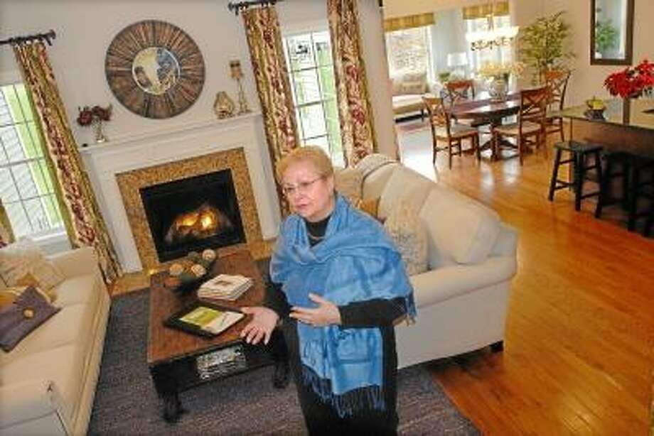 Catherine Avalone/The Middletown Press                                                                                                                                                                                                                                                        Marie Coughlin, a resident and realtor at Sonoma Woods, an over 55 active adult community on Westfield Street in Middletown stands in the livingroom of the Zinfandel cape, a 1,974 square foot home with has 2 bedrooms and 3 bathrooms and sells for $349,900.
