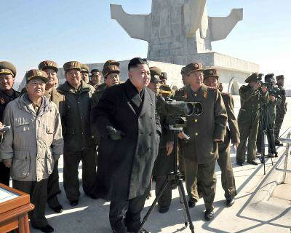 In this undated photo released by the Korean Central News Agency (KCNA) and distributed March 14, by the Korea News Service, North Korean leader Kim Jong Un watches a live ammunition firing drill by the Jangjae Islet Defense Detachment and the Mu Islet Hero Defense Detachment deployed in the southwestern sector of North Korea.