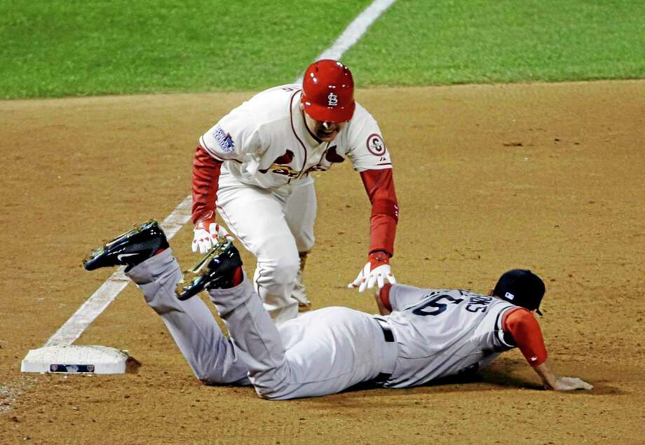 St. Louis Cardinals' Allen Craig gets tangled with Boston Red Sox's Will Middlebrooks during the ninth inning of Game 3 of baseball's World Series Saturday, Oct. 26, 2013, in St. Louis. Middlebrooks was called for obstruction on the play and Craig went in to score the game-winning run. The Cardinals won 5-4 to take a 2-1 lead in the series. (AP Photo/David J. Phillip) Photo: AP / AP