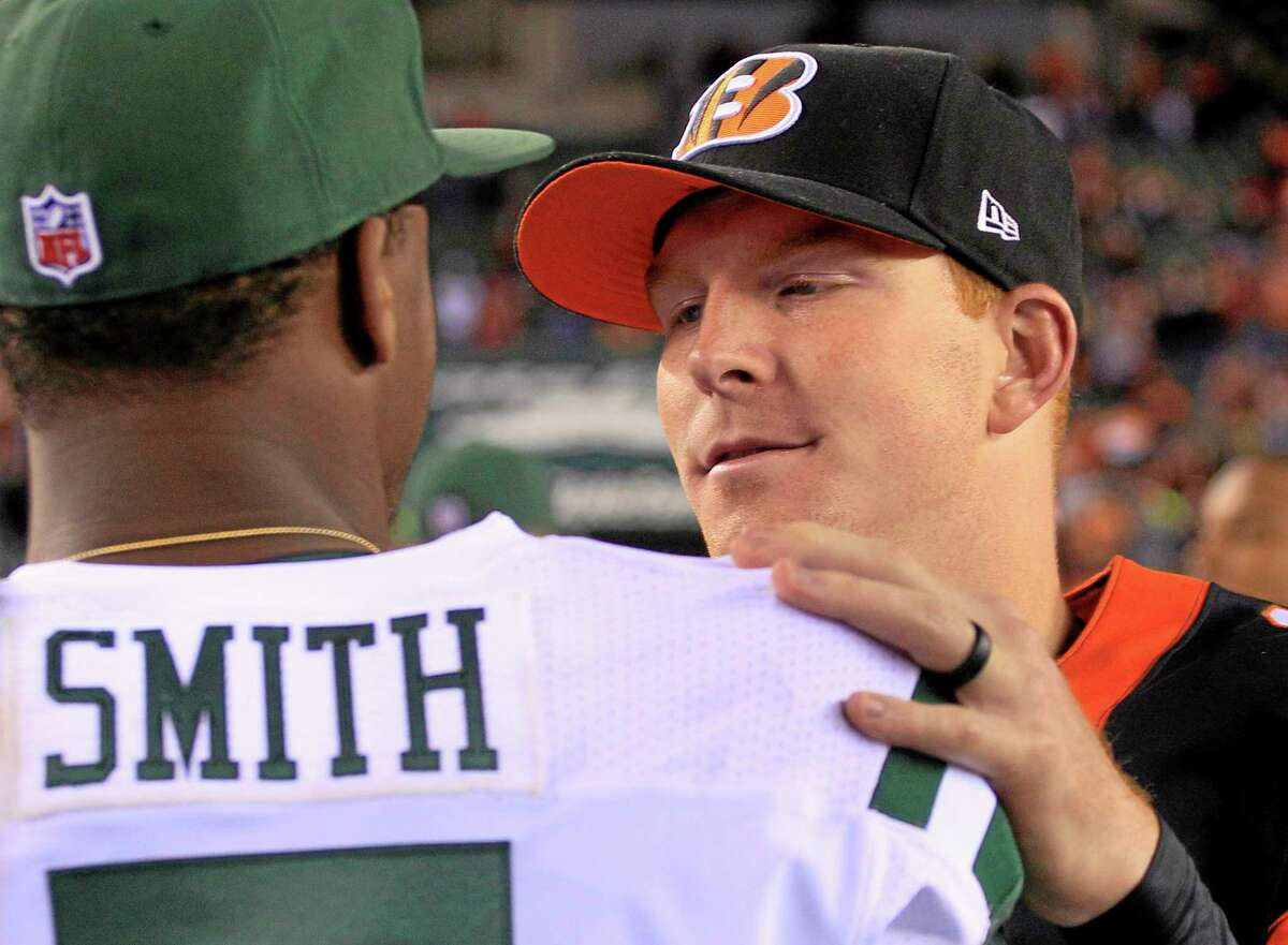 Cincinnati Bengals quarterback Andy Dalton, right, meets with New York Jets quarterback Geno Smith after the Bengals defeated the Jets 49-9.