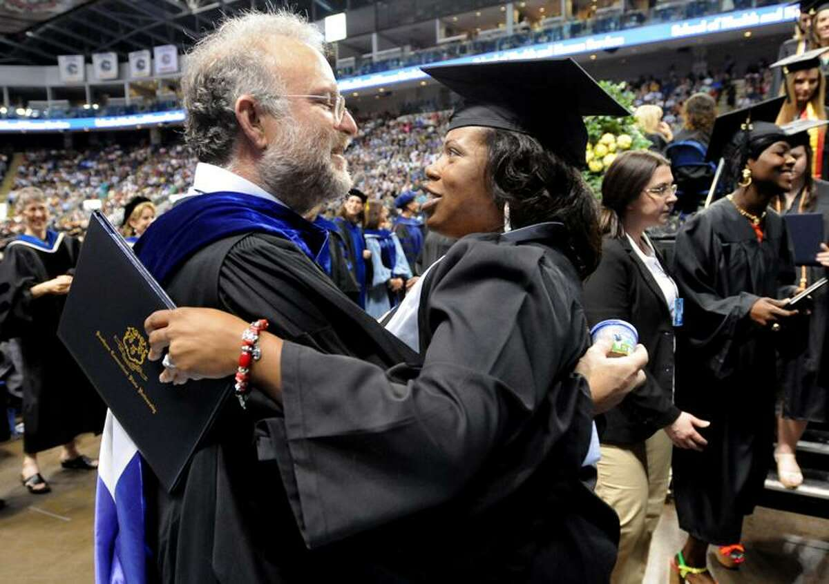 Jerry Greenfield, co-founder of Ben & Jerry's ice cream is hugged by graduate Aurelia Aleman of New Haven as Greenfield gives out ice cream at the 2013 Southern Connecticut State University Undergraduate Commencement ceremonyFriday May 17, 2013 at the Webster Bank Arena in Bridgeport, Connecticut. The ceremony featured Greenfield as the commencement speaker, who with hisfriend and business partner created an ice cream mega-business. Photo by Peter Hvizdak / New Haven Register