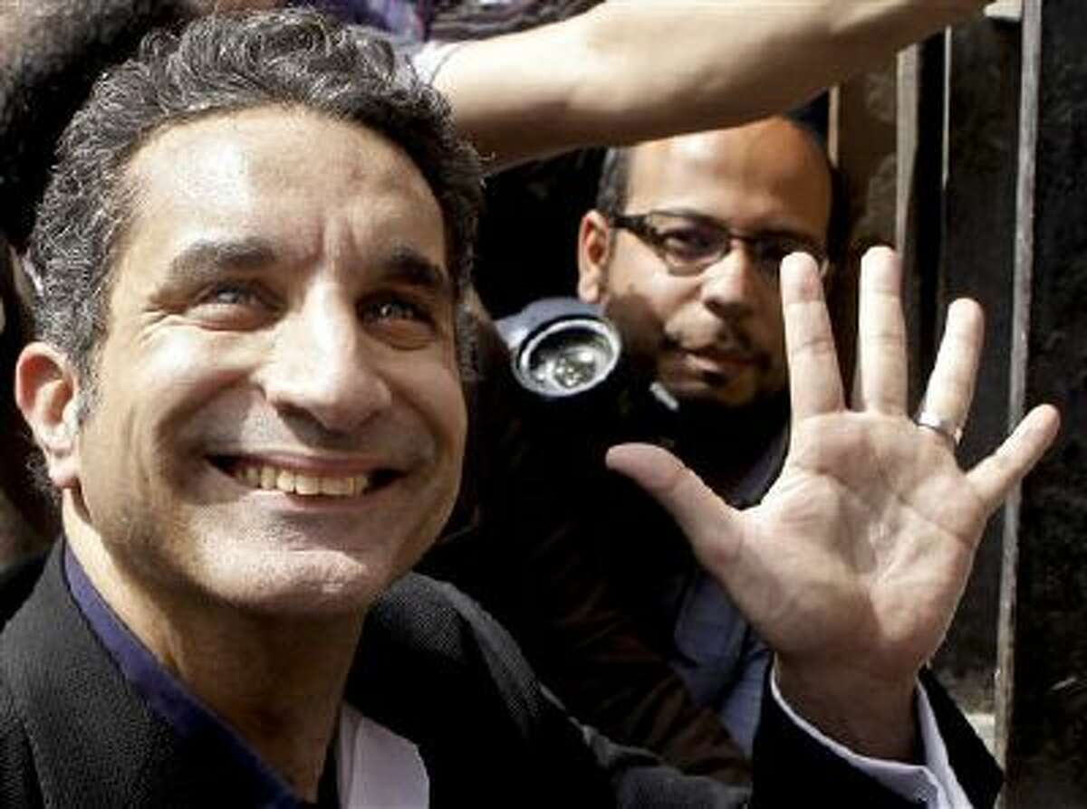 In this Sunday, March 31, 2013 file photo, Egyptian television satirist Bassem Youssef, known as Egypt's Jon Stewart, waves to his supporters as he enters Egypt's state prosecutors office to face charges for allegedly insulting Islam and the country's leader, in Cairo, Egypt. Egypt's top prosecutor has ordered an investigation into a complaint that alleges Youssef, harmed national interests by ridiculing the country's military.