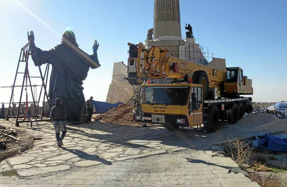 This Oct. 14, 2013 photo provided by the St. Paul's and St. George's Foundation shows workers preparing to install a statue of Jesus on Mount Sednaya, Syria. In the midst of a civil war rife with sectarianism, a 12.3-meter (40-foot) tall, bronze statue of Jesus has gone up on a Syrian mountain, apparently under cover of a truce among three factions - Syrian forces, rebels and gunmen in the Christian town of Sednaya. (AP Photo/Samir El-Gadban, St. Paul's and St. George's Foundation) Photo: AP / St. Paul's and St. George's Foundation