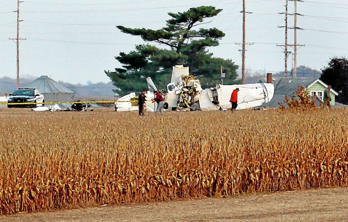 Emergency personnel work at the scene of a plane crash in a farm field near Houston County Airport in southeastern Minnesota on Friday, Nov. 1, 2013. Three people were killed in the crash that was and one person in critical condition according to authorities. (AP Photo/The La Crosse Tribune, Peter Thomson)