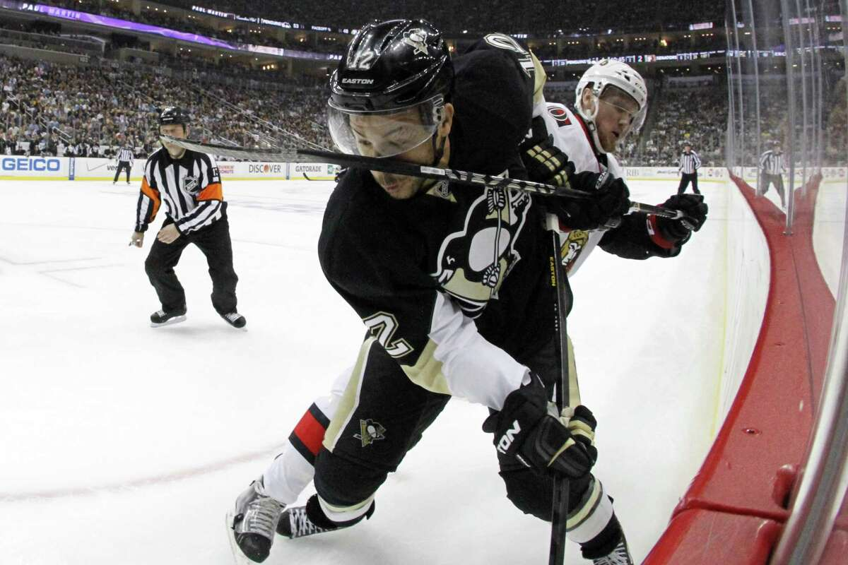 Pittsburgh Penguins' Jarome Iginla (12) gets a stick in the face from Ottawa Senators' Erik Condra (22) in the second period of Game 2 of an NHL hockey Stanley Cup second-round playoff series, in Pittsburgh on Friday, May 17, 2013. The Penguins won 4-3. (AP Photo/Gene J. Puskar)