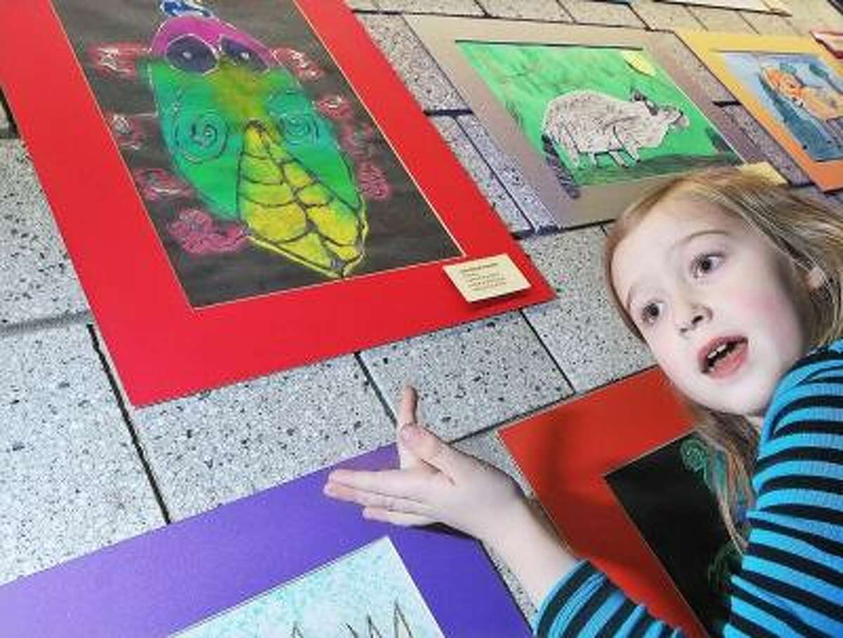 Catherine Avalone/The Middletown Press Gwendolyn Weeden, 7, a second grade student at Valley View Elementary School in Portland explains how she created her symmetrical insect using pastel and white glue at the opening of the Student Art Month show at Portland Public Library at 20 Freestone Avenue.
