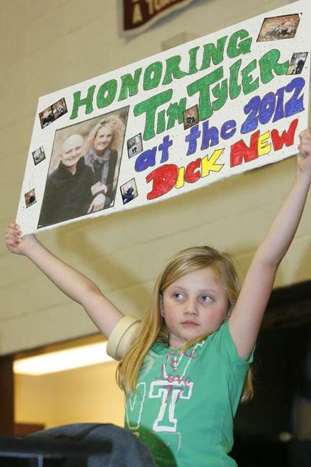 Dispatch Staff Photo by JOHN HAEGER (Twitter: @OneidaPhoto)   Emma Tyler, then 7, holds up a sign honoring her father Tim Tyler before the start of the  finals of the  Canastota Dick New Tournament on Saturday Jan. 7, 2012 in Canastota.