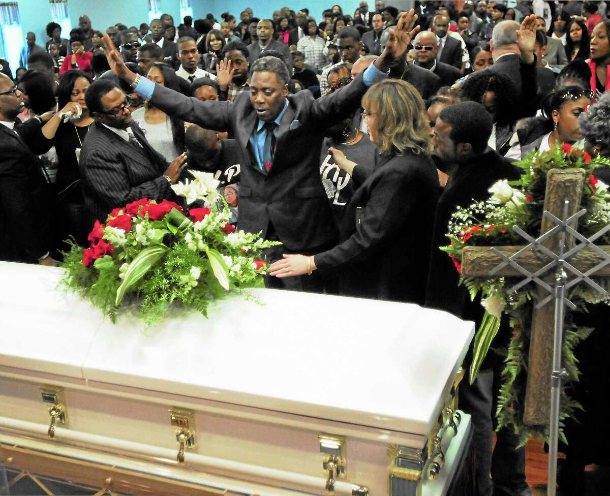 Gregory Fulcher Sr. of West Haven stands over the casket of his daughter, Erika Renee Robinson, at Robinson's funeral Saturday at the Agape Christian Center in New Haven.