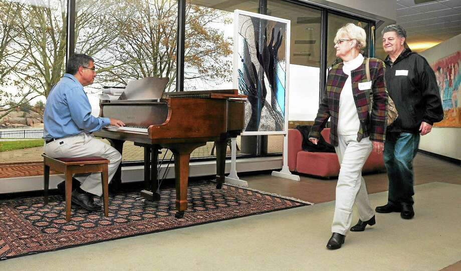 Sal Anastasio of East Haven volunteers twice a week at Connecticut Hospice in Branford, playing the piano in the lobby as staff, patients and families, like Annette and Tony Signore of Branford, pass by. Photo: Mara Lavitt — New Haven Register         / Mara Lavitt