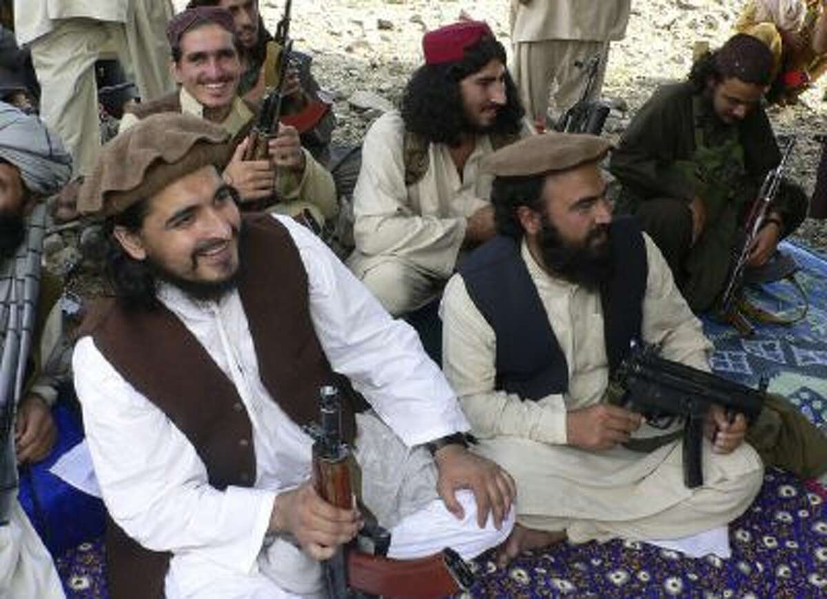 In this file photo taken Sunday, Oct. 4, 2009, new Pakistani Taliban chief Hakimullah Mehsud, left, is seen with his comrade Waliur Rehman, front center, during his meeting with media in Sararogha of Pakistani tribal area of South Waziristan along the Afghanistan border.