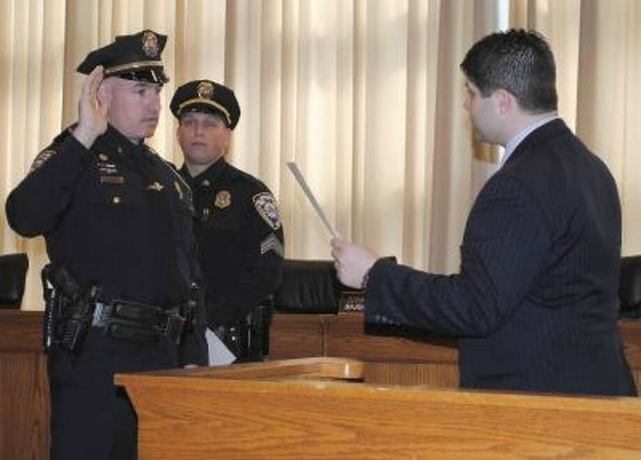 Viktoria Sundqvist/The Middletown Press Middletown Mayor Daniel Drew swears in Richard Davis to his new lieutenant position in a ceremony at Council Chambers Friday.