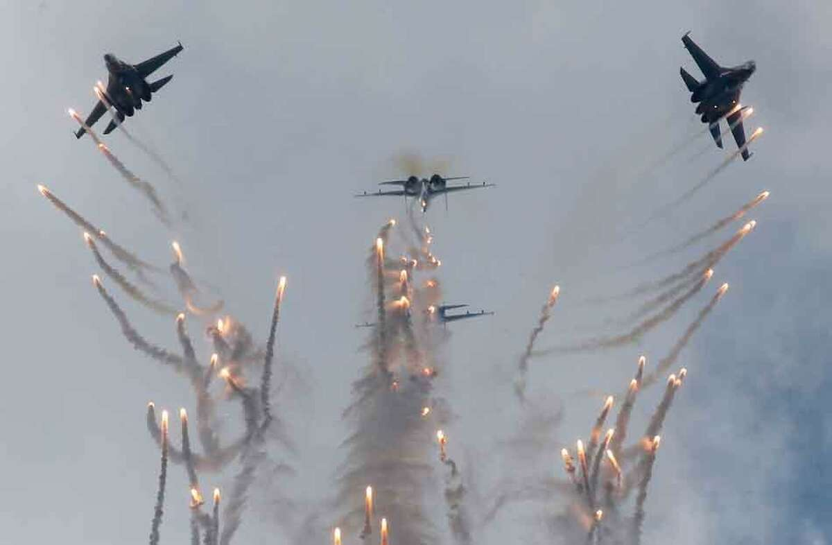 Su-27 jets of aerobatics team Russkiye Vityasy, or Russian Knights, release decoys as they perform aerial demonstrations during the International Maritime Defense show in St.Petersburg, Russia, Sunday, July 7, 2013. (AP Photo/Dmitry Lovetsky)