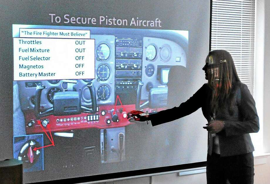 Melanie Folcik, program coordinator for Redline Elements, gives a presentation on the workings of aircraft controls to Milford firefighters recently. Photo: Peter Casolino — New Haven Register