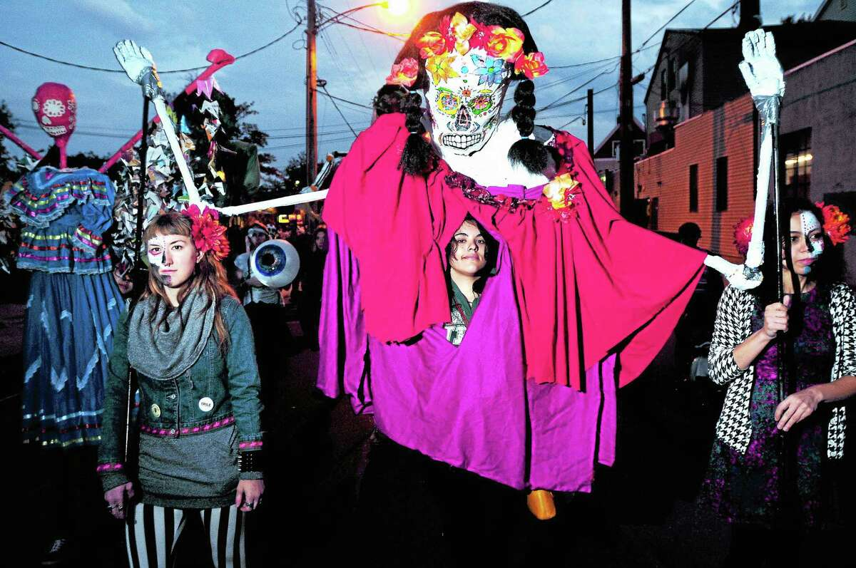 From left, Leigh Kern, Hannah Jellinek and Eda Uca carry a puppet, made by Jellinek, in the Day of the Dead parade Saturday.