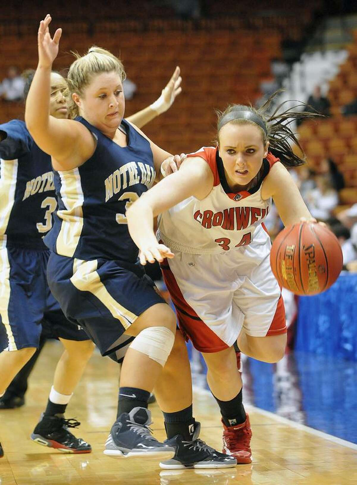 Catherine Avalone/The Middletown Press Cromwell senior Kelly Flanigan drives past Notre Dame senior McKenzie Stone at Mohegan Sun Friday night. Cromwell defeated Notre Dame-Fairfield 42-28 for the Class M Championship title.