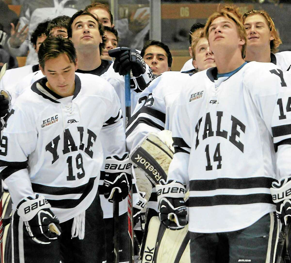 Yale players look up as the 2013 NCAA men's hockey national championship banner is raised at Yale's Ingalls Rink before Friday night's game against St. Lawrence.