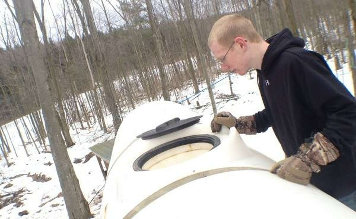 John Haeger @OneidaPhoto on Twitter/Oneida Daily Dispatch VVS FFA member Zack Wheelock collects.sap from the collection tank in the wood lot to be taken back to the sap house and boiled down into maple sypra on Thursday, March 7, 2013
