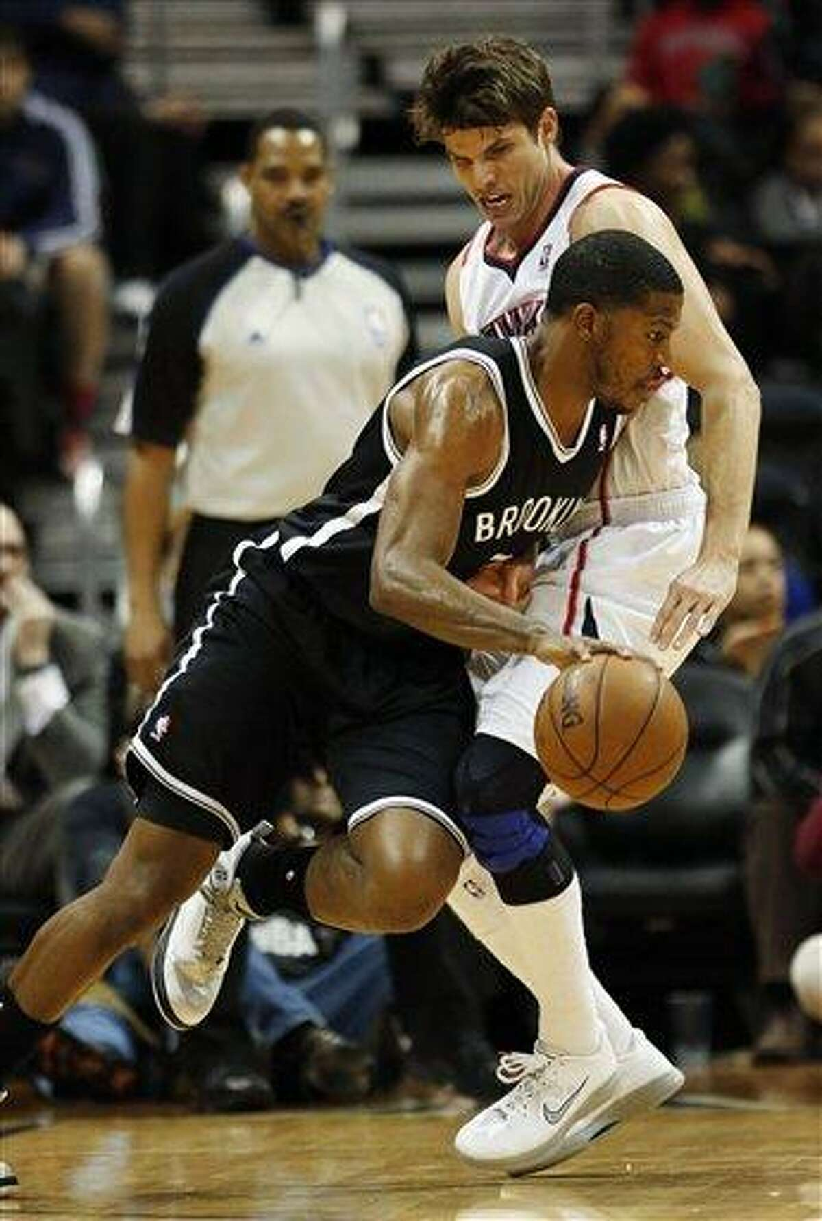 Brooklyn Nets shooting guard Joe Johnson, foreground, drvies against Atlanta Hawks shooting guard Kyle Korver in the first half of an NBA basketball game on Wednesday, Jan. 16, 2013, in Atlanta. (AP Photo/John Bazemore)