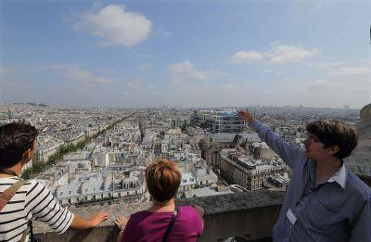 Tour guide David (R) gives explanations to visitors as they look at the Paris skyline from the zinc-topped terrace of the Tour Saint-Jacques in Paris July 5, 2013. It's not for the short of breath or those weak in the knees, but the dizzying 360-degree vista of Paris from the Tour Saint-Jacques is one of the best-kept secrets of the French capital. For one good reason: this flamboyant 16th-century Gothic tower, a famous passing point for pilgrims headed to Santiago de Compostela in Spain, had been closed to the public for most of its 500-year history.Now open to tourists until September 15, the 62-metre (203 foot) tower offers stunning bird's eye views - provided you have the energy to walk up its claustrophobic 300-step spiral staircase. REUTERS/Philippe Wojazer (FRANCE - Tags: SOCIETY TRAVEL)