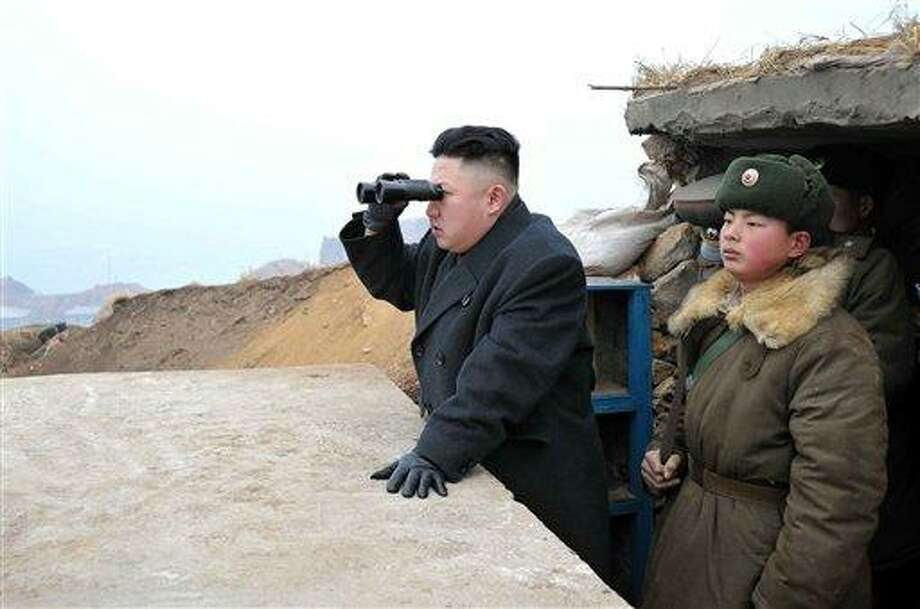In this March 7, 2013 photo released by the Korean Central News Agency (KCNA) and distributed March 8, 2013 by the Korea News Service, North Korean leader Kim Jong Un, center, uses binoculars to look at the South's territory from an observation post at the military unit on Jangjae islet, located in the southernmost part of the southwestern sector of North Korea's border with South Korea.  Seven years of U.N. sanctions against North Korea have done nothing to derail Pyongyang's drive for a nuclear weapon capable of hitting the United States. They may have even bolstered the Kim family by giving their propaganda maestros ammunition to whip up anti-U.S. sentiment and direct attention away from government failures.  Defense Secretary Chuck Hagel plans to announce Friday that the Obama administration has decided to add 14 interceptors on the West Coast to the U.S.-based missile defense system. (AP Photo/KCNA via KNS) JAPAN OUT UNTIL 14 DAYS AFTER THE DAY OF TRANSMISSION Photo: AP / KCNA VIA KNS