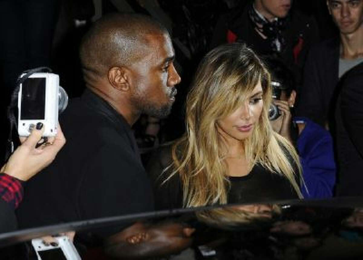 In this Sept. 29, 2013 photo, Kanye West, left, and Kim Kardashian leave after attending Givenchy's ready-to-wear Spring/Summer 2014 fashion collection in Paris.