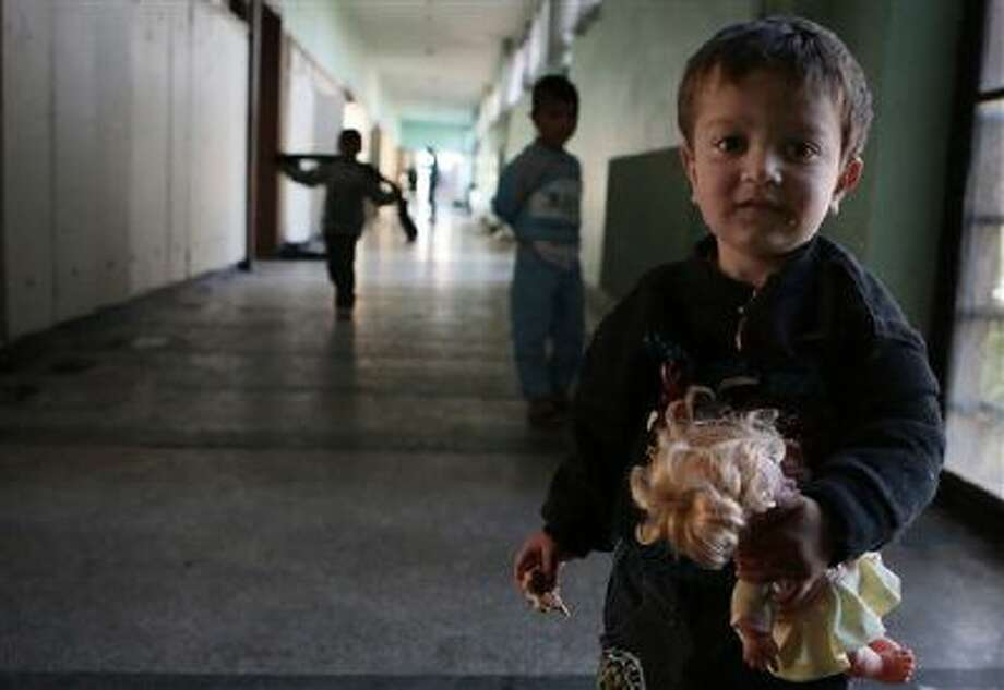 A Syrian boy holds a doll in the corridors of a recently opened refugee camp sheltered in an old school in the outskirts of the capital Sofia. The impoverished Balkan state of Bulgaria has seen a considerable refugee influx over the past months. Photo: AP / AP