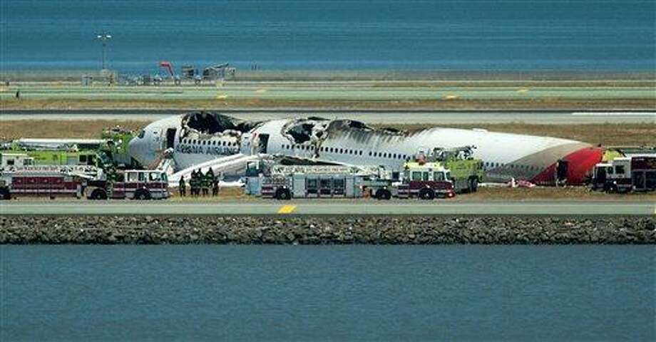 Fire crews respond to the scene where Asiana Flight 214 crashed at San Francisco International Airport on Saturday, July 6, 2013, in San Francisco. (AP Photo/Noah Berger) Photo: AP / FR34727 AP