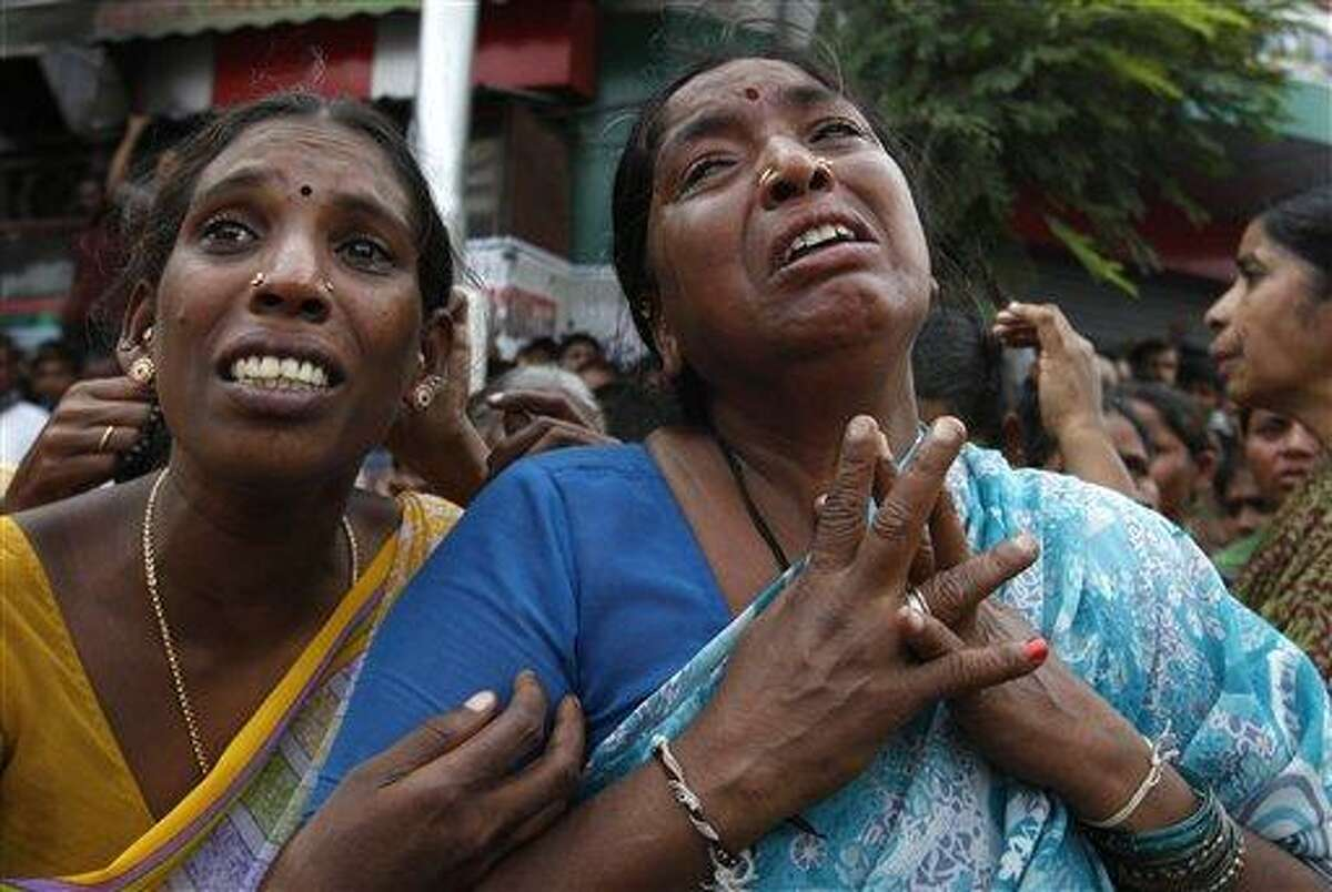 Unidentified Indian women cry at the site of a building collapse where their relatives are stuck inside the debris, in Hyderabad, India, Monday, July 8, 2013. An official says a two-story hotel has collapsed in southern India, killing at least 10 people and injuring 12 others.(AP Photo/Mahesh Kumar A.)