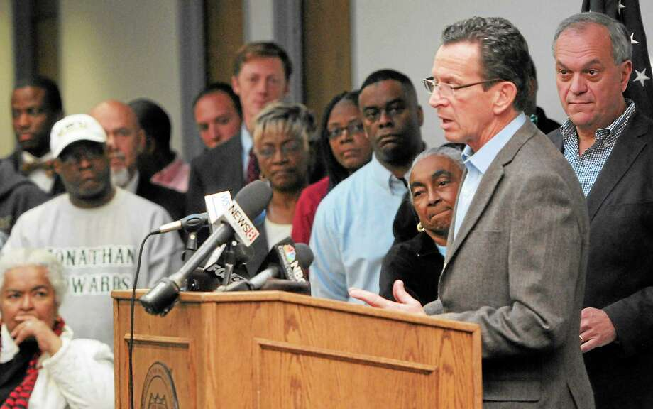 (Peter Hvizdak — Register)Connecticut Governor Dannel P. Malloy speaks at a  press conference Saturday afternoon October 26, 2013 at NHPD headquarters as New Haven Police investigate the crime scene where one woman is dead, two people are listed in critical condition and three are being treated for non-life threatening wounds and injuries after a shooting at the Key Club Cabaret at 85 Saint John St. near Hamilton St.  Saturday morning October 26, 2013. New Haven Mayor John DeStefano, Jr.  is at right and various New Haven community leaders are at left. Photo: New Haven Register / ©Peter Hvizdak /  New Haven Register