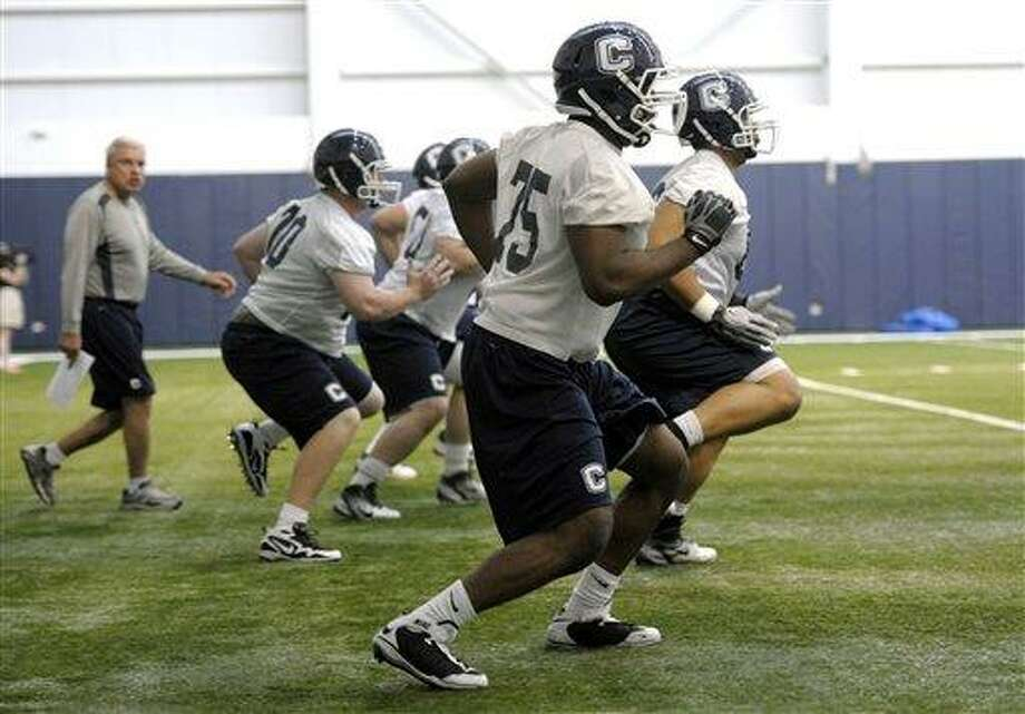 Connecticut offensive coordinator George DeLeone, rear left, runs drills during the first day of the team's spring NCAA college football practice, Tuesday, March 20, 2012, in Storrs, Conn.  (AP Photo/Sean D. Elliot, The Day) Photo: ASSOCIATED PRESS / AP2012