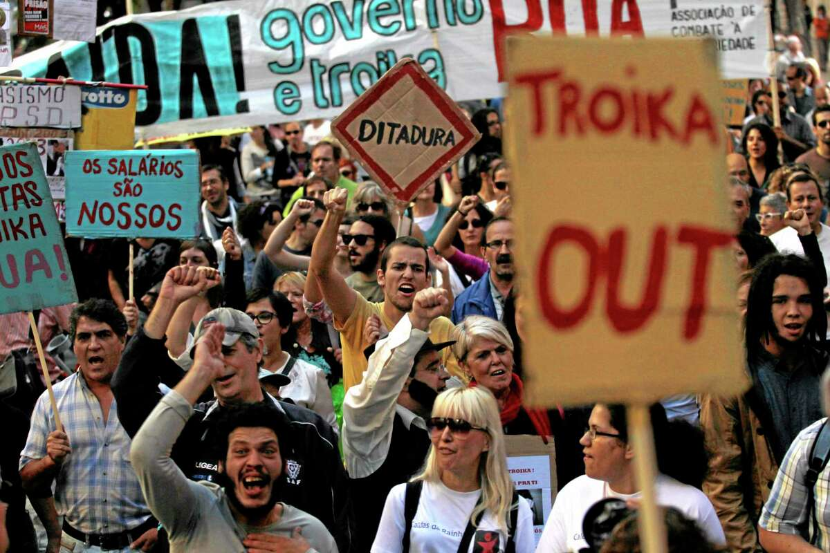 """People march towards the Portuguese parliament during a demonstration against austerity measures taken by the Portuguese government linked to an euro 78 billion ($107.6 billion) bailout agreement in 2011, in Lisbon, Saturday, Oct. 26, 2013. The government and the so-called Troika of bailout creditors, Portugal's fellow eurozone members, insist the country must repair its finances to restore investor faith. Placards read in Portuguese: """"Dictatorship,"""" """"The salaries are ours"""" and """"There is a way! Government and Troika Out!"""". (AP Photo/Francisco Seco)"""