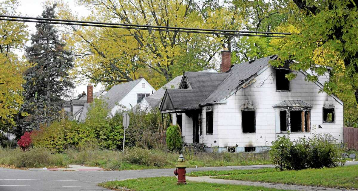 Burned out and vacant homes in Detroit. Mich. Saturday Oct. 26, 2013. Detroit Public Schools and The Detroit Fire Department teamed up to board up old homes and clear out blighted structures and overgrowth in the Burt and Tireman neighborhood. (AP Photo/The Detroit News, Todd McInturf)