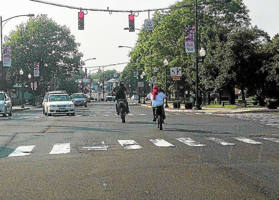 This September 10 photo shows two riders running a red light on Main Street at Messina Drive in East Haven. Photo: Evan Lips - New Haven Register