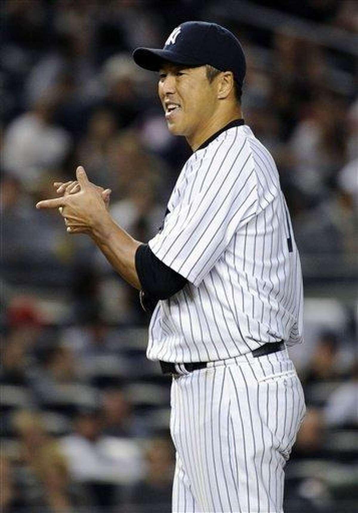 New York Yankees pitcher Hiroki Kuroda rubs up a new ball during the seventh inning of a baseball game against the Toronto Blue Jays Friday, May 17, 2013, at Yankee Stadium in New York. (AP Photo/Bill Kostroun)