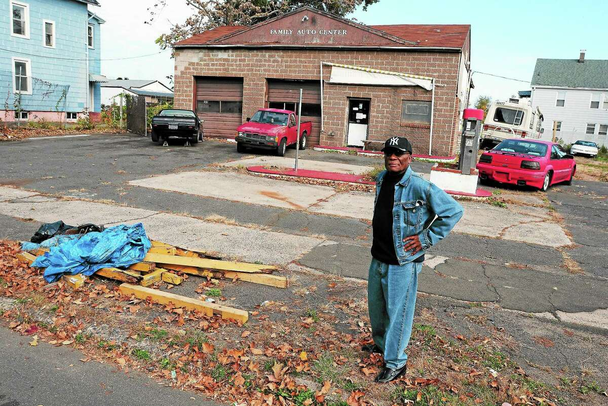 Orlander Highsmith of Shelton Avenue in Hamden stands by an abandoned auto repair shop on Goodrich Avenue that he says is an eyesore in his neighborhood.