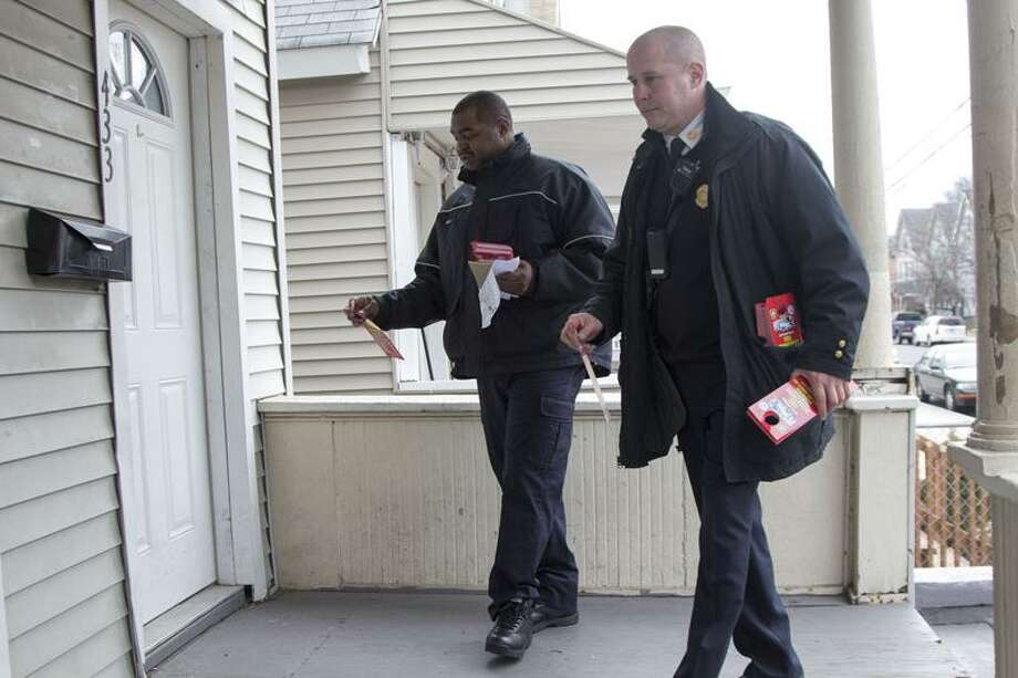 New Haven Fire Department Assistant Chief Patrick Egan and firefighter Michael Neal hang recruitment flyers on doors in the Hill Fire District on Tuesday. The department is looking to hire between 80-100 entry-level firefighter positions out of the next recruitment class. Photo by Rich Scinto/Register