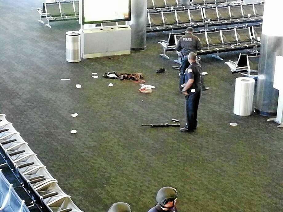 In this photo provided to the AP, which has been authenticated based on its contents and other AP reporting, police officers stand near an unidentified weapon in Terminal 3 of the Los Angeles International Airport Friday. Photo: The Associated Press          / AP