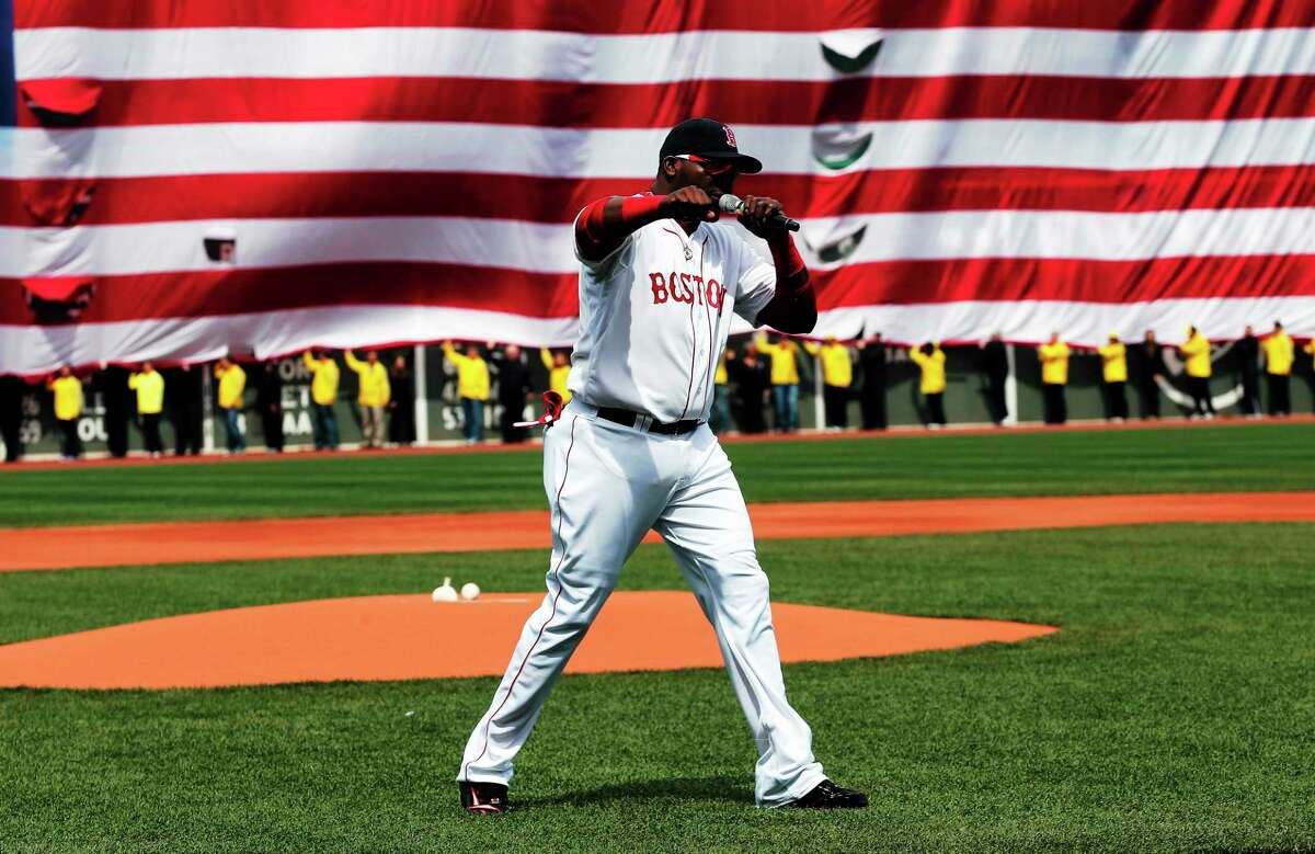 Boston Red Sox designated hitter David Ortiz pumps his fist in front of an American flag and a line of Boston Marathon volunteers after addressing the crowd before a game against the Kansas City Royals at Fenway Park on April 20.