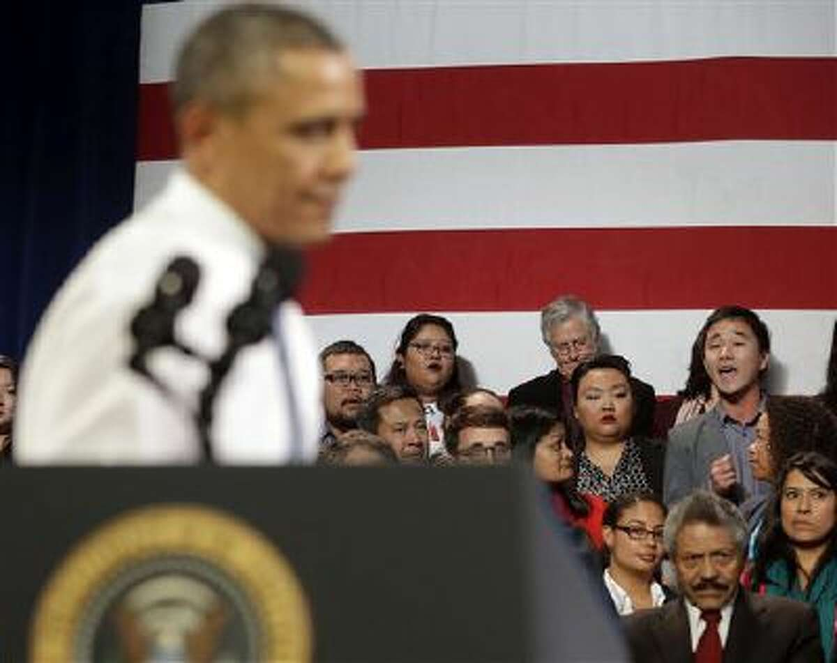 President Barack Obama, left, stops his speech and turns around in response to an unidentified man, right, who heckled him about anti-deportation policies in San Francisco. 2013 was a tough year for Obama on many fronts.