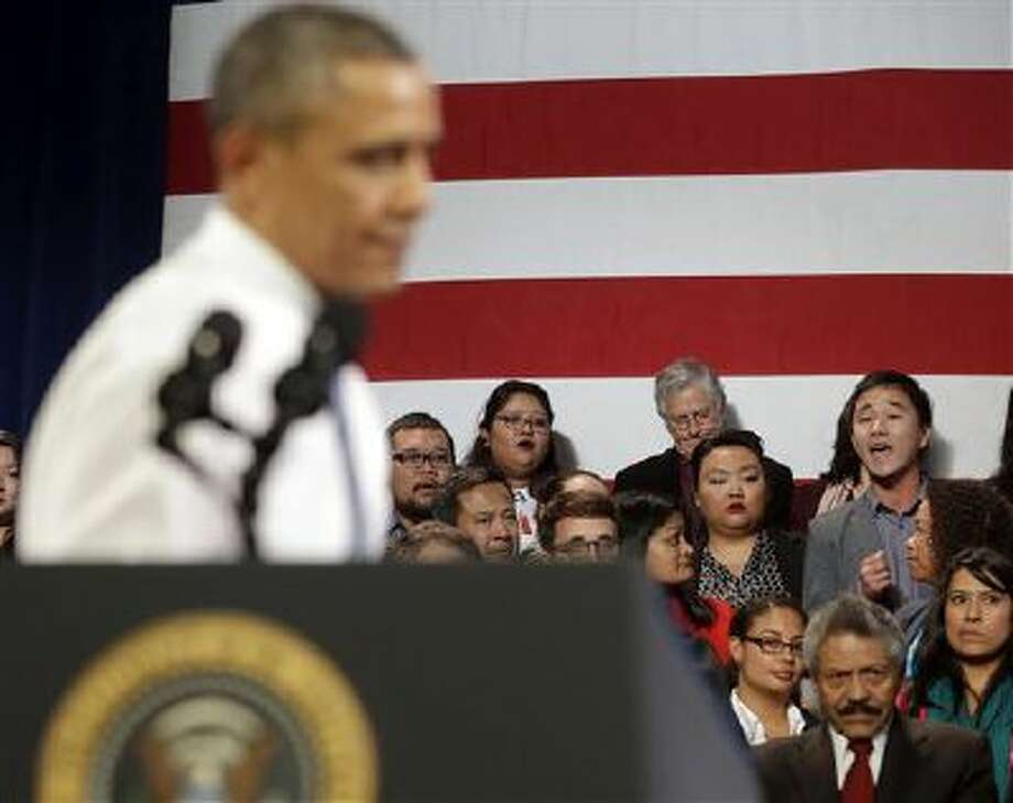 President Barack Obama, left, stops his speech and turns around in response to an unidentified man, right, who heckled him about anti-deportation policies in San Francisco. 2013 was a tough year for Obama on many fronts. Photo: AP / AP