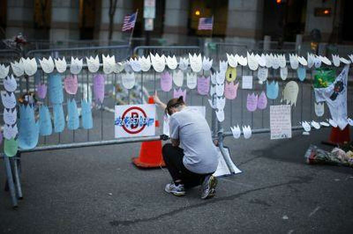 A woman kneels and cries in front of a memorial to the Boston Marathon bombings victims, at the barricades surrounding the scene in Boston, Massachusetts April 18, 2013.