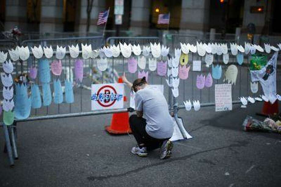 A woman kneels and cries in front of a memorial to the Boston Marathon bombings victims, at the barricades surrounding the scene in Boston, Massachusetts April 18, 2013. Photo: REUTERS / X90051
