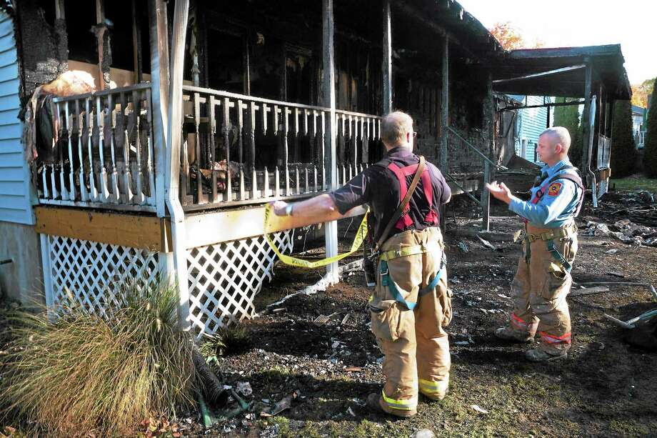 Firefighters tape off the back porch that was severely burned in a fire this morning at 81 Bird Lane in Milford Oct 25. Photo: VM Williams — New Haven Register
