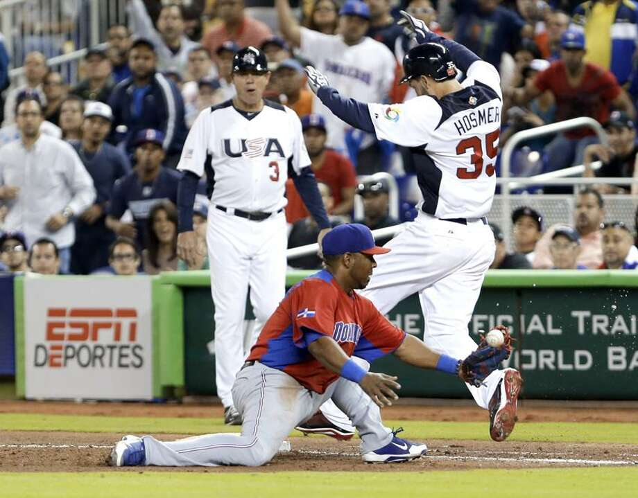 United States' Eric Hosmer (35) is safe at first base as Dominican Republic first baseman Edwin Encarnacion is unable to hold on to the ball during the sixth inning of a second-round game of the World Baseball Classic in Miami, Thursday, March 14, 2013. Jose Reyes was charged with a throwing error. (AP Photo/Wilfredo Lee) Photo: AP / AP
