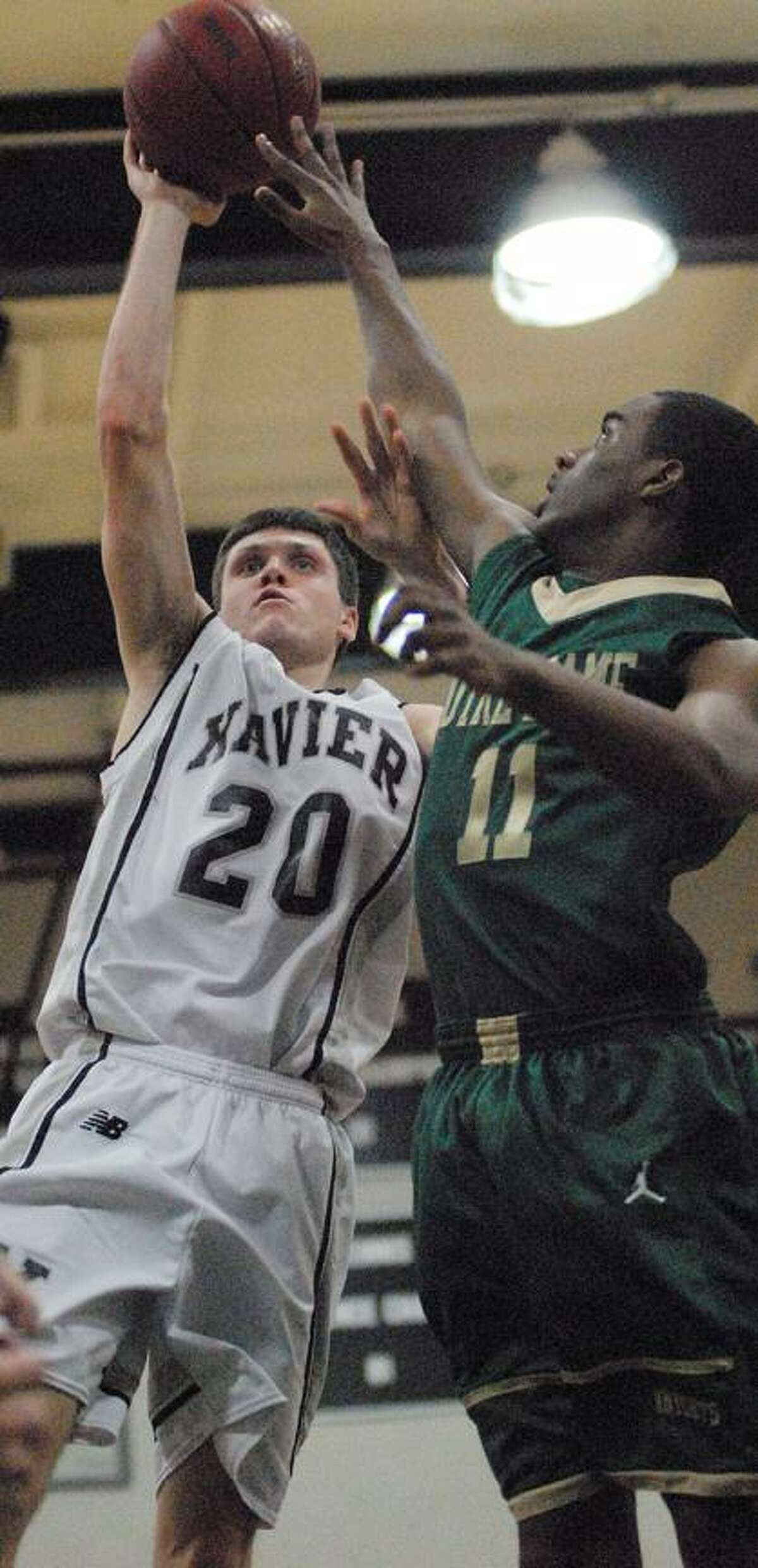 Catherine Avalone/The Middletown Press Xavier senior captain James Sullivan elevates for a shot as Notre Dame's Kevin Walton defends Tuesday night in Middletown. Notre Dame defeated Xavier 55-52.